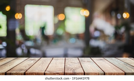Empty wood table top and blurred coffee shop, cafe and restaurant interior background - can used for display or montage your products.