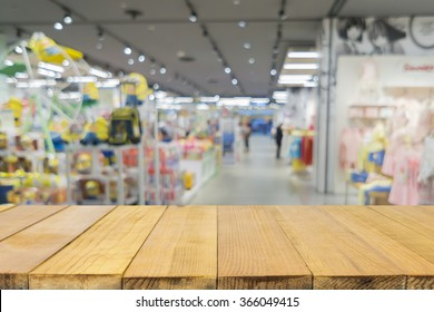 Empty Wood table top with blurred background of  toys department store,Natural bokeh shopping mall Toy Store,vintage color.- can be used for montage or display your products