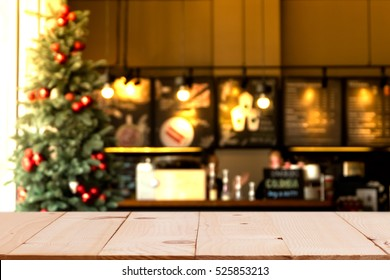 Empty wood table top with blurred chistmas holiday background with  coffee shop (cafe) and restaurant shop interior background in winter season -  for your product display or montage.