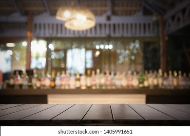 Empty wood table top with Defocused background and bottles of restaurant or bar background. Using for Mock up template for craft display of your design.