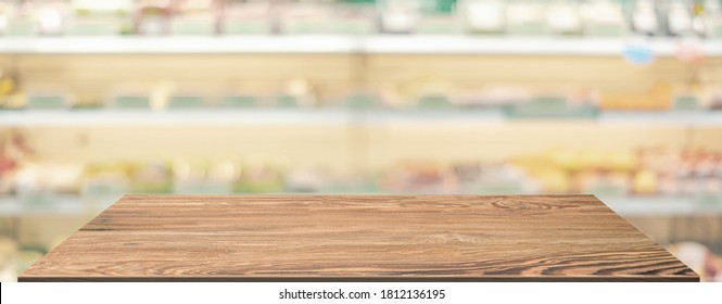 Empty wood table top food stand with blur grocery product shelf background bokeh light,Mockup for display of product,Banner for advertise on food online media
