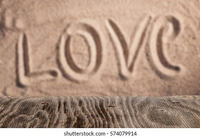 Empty wood table top with love written in sand as Valentines background for display your product