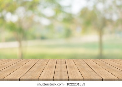 Empty wood table top on nature green blurred background at garden,space for montage show products
