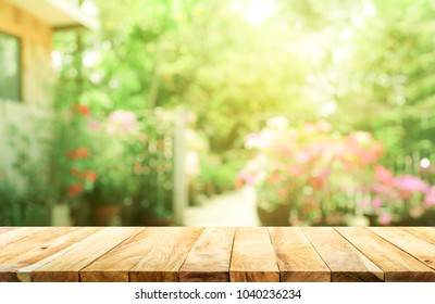 Empty wood table top on blur abstract green from garden and house background. For montage product display