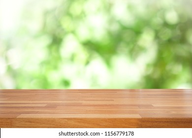 Empty of wood table top on blur of abstract green from garden with sunlight and curtain window , product display, Ready for product montage.