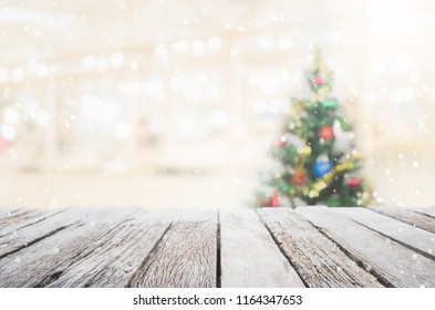 Empty wood table top on blur with bokeh Christmas tree background with snowfall - can be used for display or montage your products.