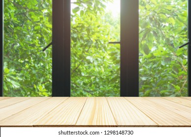 Empty wood table top on black metallic window frame with green tree nature background