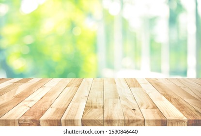 Empty wood table top on blur abstract green garden from window view background.For montage product display or design key visual layout