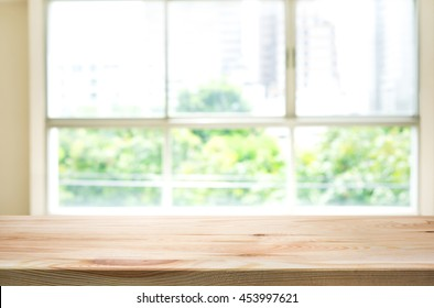 Empty of wood table top on blur of window glass and abstract green from garden with city view in the morning background.For montage product display or design key visual layout background.