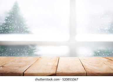 Empty wood table top on blur window view with pine tree in snow fall of morning winter season.For christmas day background and new year concept.