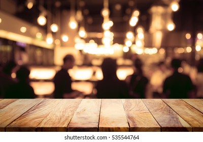 Empty wood table top on blur light bokeh in dark night cafe restaurant background .Lifestyle and celebration concept