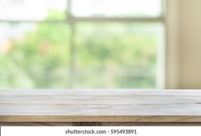Empty wood table top on blur abstract green garden from window view in the morning.For montage product display or design key visual layout