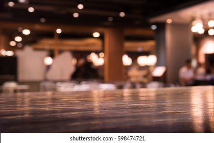 Empty wood table top on blur cafe (restaurant) in dark night with light background/selective focus.For montage product display