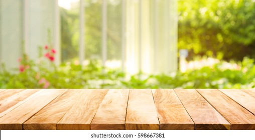 Empty wood table top on blur abstract green from garden and house in morning background.For montage product display or design key visual layout