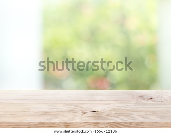 Empty wood table top on blur abstract green garden from window view in the morning. For montage product display or design key visual layout