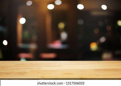 empty wood table top over blur night light in restaurant cafe background.