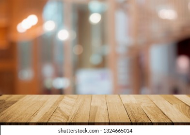 empty wood table top over blur in restaurant cafe background.