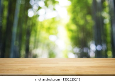 empty wood table top over blur outdoor green nature background.