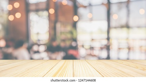 Empty Wood table top with Restaurant cafe or coffee shop interior with customer blur abstract vintage style bokeh light for montage product display background