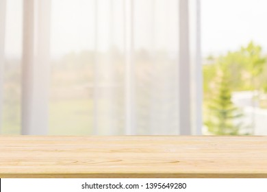 Empty wood table top with window curtain abstract blur background for product display