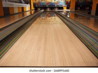 Empty wooden alley lane in modern bowling club