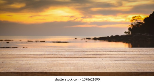 Empty wooden bar counter with blurred sunset beach background. Using for Mock up template for craft display of your design.