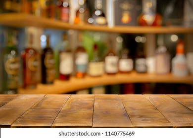Empty wooden bar counter with Defocused background and bottles of restaurant, bar or cafeteria background. Using for Mock up template for craft display of your design,Banner for advertise of product.