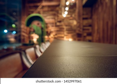 Empty wooden bar counter with defocused background and bottles of restaurant, bar or cafeteria background. Using for Mock up template for craft display of your design product.