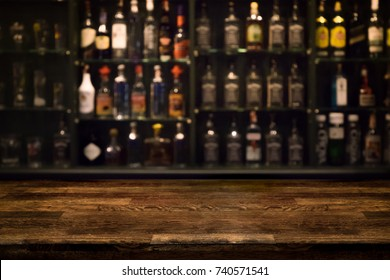 Empty wooden bar counter with defocused background and bottles of restaurant, bar or cafeteria background /for your product display