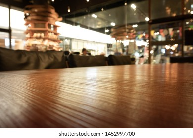 Empty wooden bar counter with reflect on blur of lighting in night background and bottles of restaurant, bar or cafeteria background. Using for Mock up template.