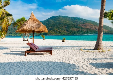Empty wooden beach chairs with parasol on the beach with coconut tree in Phuket, Thailand with parasol on the beach with coconut tree in Phuket, Thailand