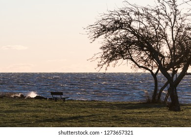 Empty wooden bench by seaside with a stormy water