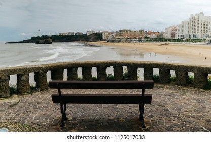 Empty wooden bench close up in scenic seascape on atlantic coastline in blue sky, biarritz, basque country, france.