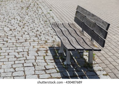 empty wooden bench on street in summer day