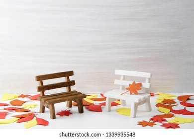 The empty wooden bench on the white footpath covered with fallen leaves is all miniature