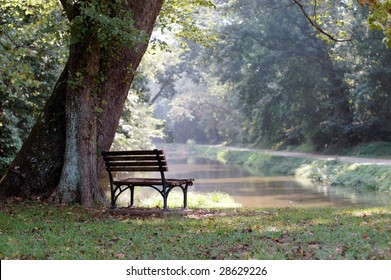 An empty wooden bench over looks a river on a sunny summer day.