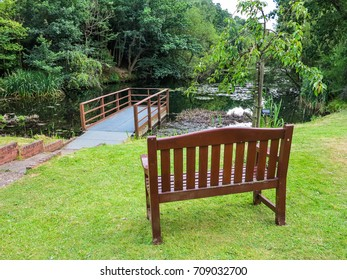 An empty wooden bench overlooking a pond in the UK