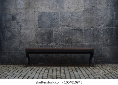 An empty wooden bench in a room with a gray stone  wall.