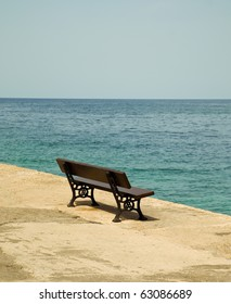 Empty wooden bench with a viewpoint looking out to sea.