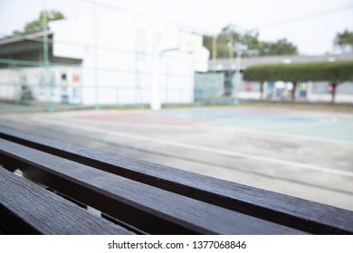 empty wooden bleachers with blurred basketball court background.