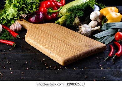 empty wooden board mockup and fresh vegetables on wooden black background
