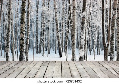Empty wooden board table and birch trees in snow-covered winter wood