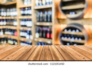 Empty wooden board table in front of blurred background. Perspective of luxury wooden wine shelf in liquor store can be used for display a products or advertise text