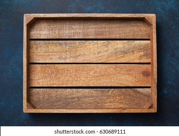 Empty wooden box on blue background. View from above. Copy space