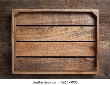 empty wooden box on old wooden background (top view, dark)