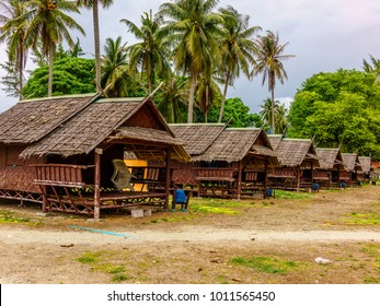 Empty wooden bungalows in a blur background of coconut trees and surrounding trees from behind in Lipe Island, Satoon province, Thailand