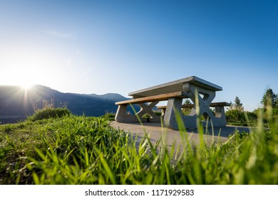 An empty wooden & cement picnic table sits on top of a hill overlooking the mountains across Columbia Lake near Fairmont Hot Springs, Canada, with the sun just rising above the peaks in the morning.