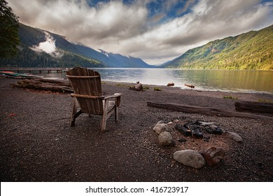 Empty wooden chair next to a burnt out camp fire beside Lake Crescent in Washington State.