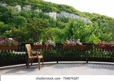 Empty wooden chair on sunny terrace decorated of flowers against mountain.