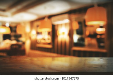 Empty wooden counter on blurry bar interior backgroud. Montage concept